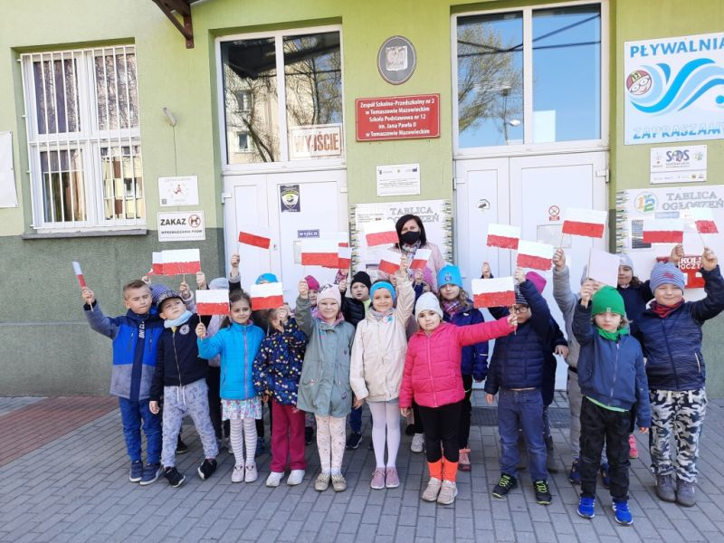 Na zdjęciu dzieci ze Szkoły Podstawowej nr 12 pozujące z flagami biało-czerwonymi przed budynkiem szkoły