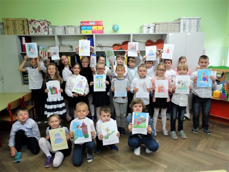 Na zdjęciu dzieci ze SP nr 12 prezentujący prace plastyczne na temat patrona szkoły - Jana Pawła II